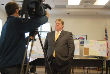 After the release of the 2012-14 Reclassification and Realignment, Dr. Mark Cousins, the athletic director, gives an interview to a local cable news station. The maps that the staff creates for each district within a conference stand in the background.